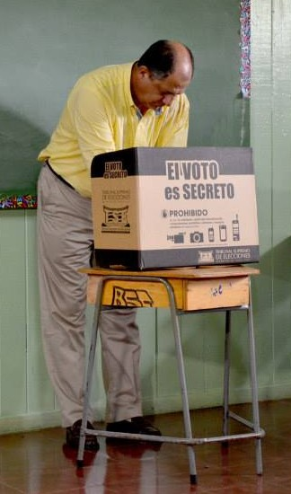 Luis Guillermo Solis, then-President of Costa Rica, votes behind a privacy screen Luis Guillermo Solis, elecciones abril 2014.jpg
