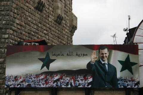 Billboard with a portrait of Bashar al-Assad and the text 'Syria is protected by God' on the old city wall of Damascus in 2006 Syria.BasharAlAssad.02.jpg