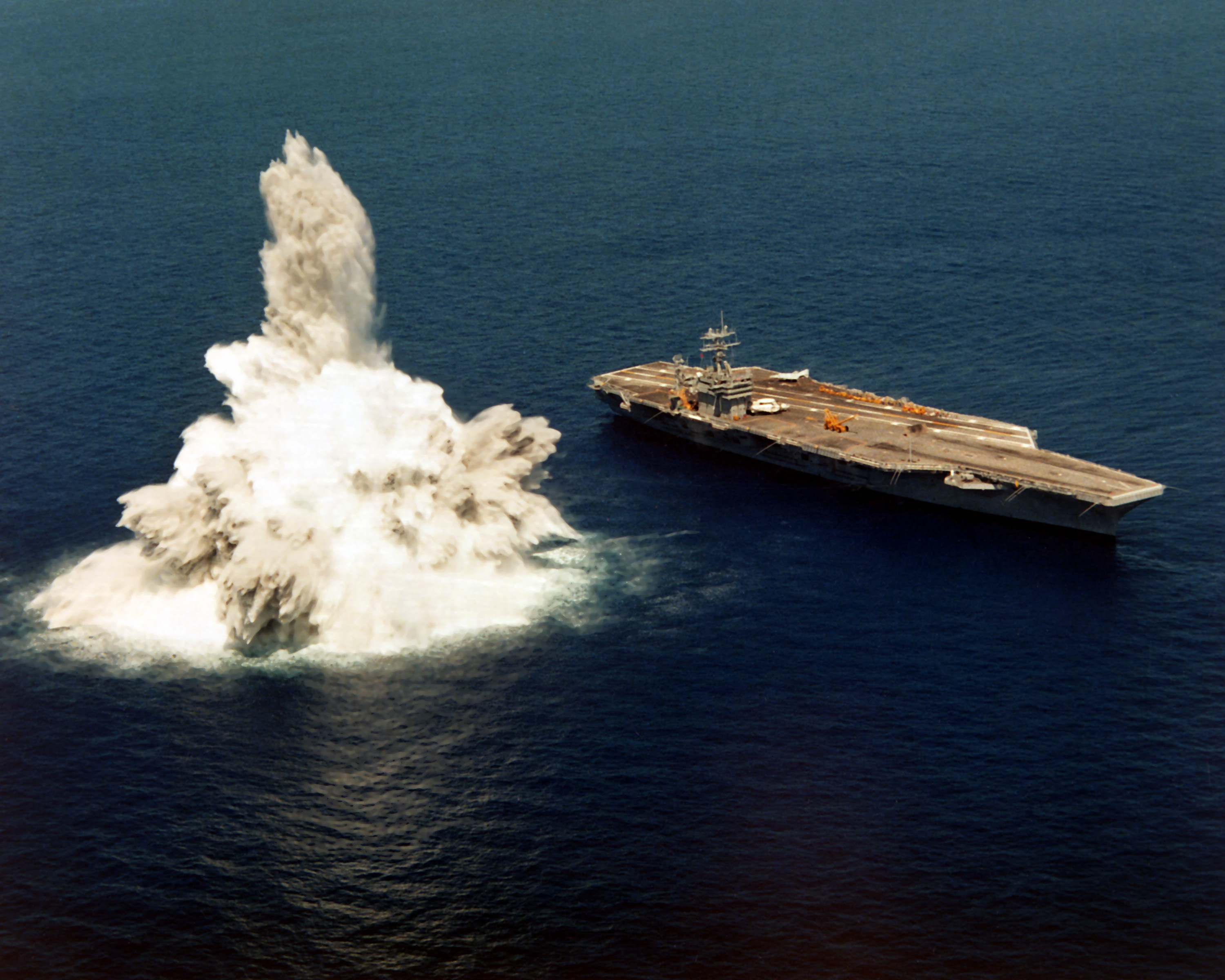 An underwater explosion in the ocean next to an aircraft carrier.