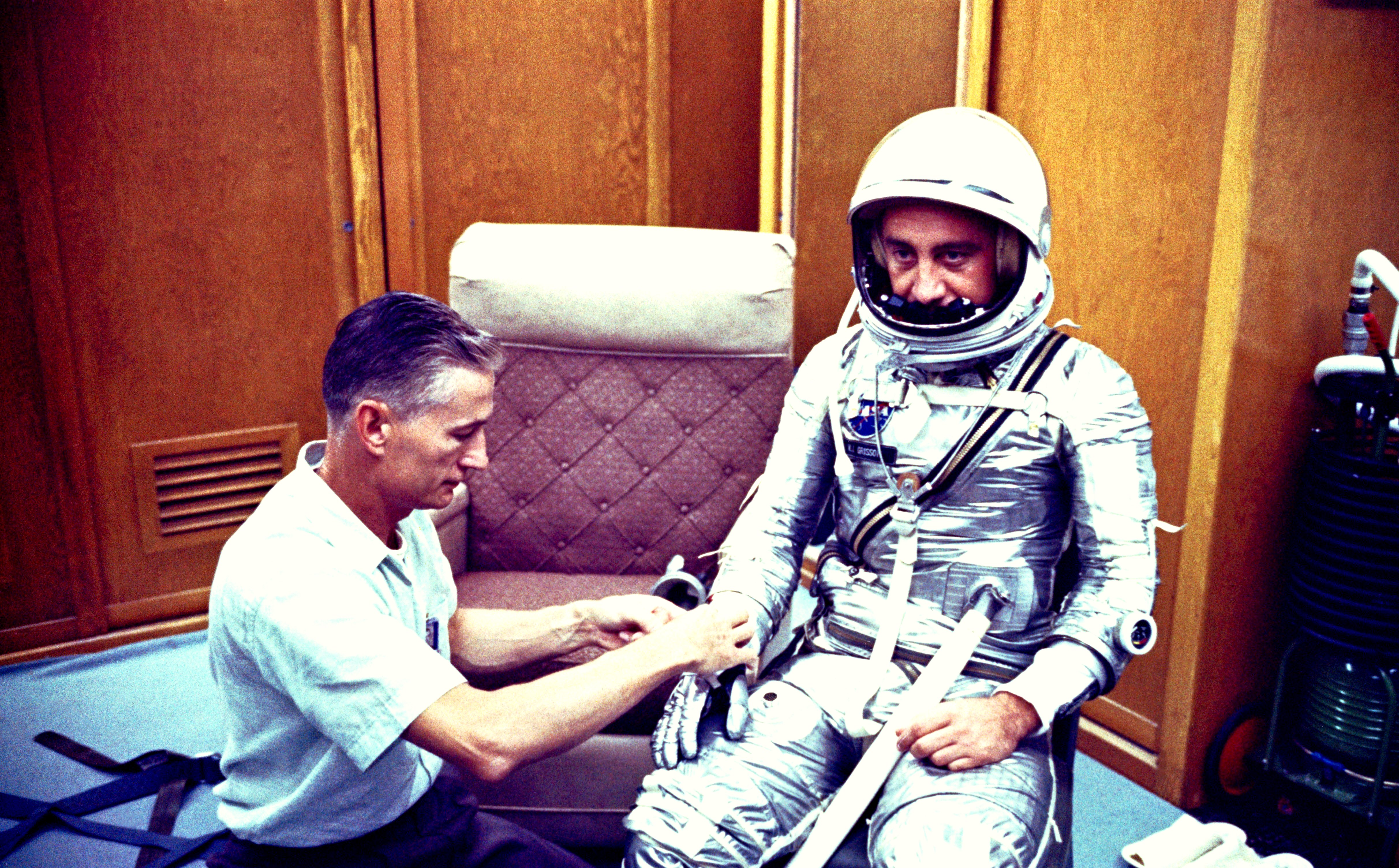 the Mercury-Redstone 4 (MR-4) mission, astronaut Virgil I. (Gus) Grissom chats with spaceflight equipment specialist Joe W. Schmidt in the personal equipment