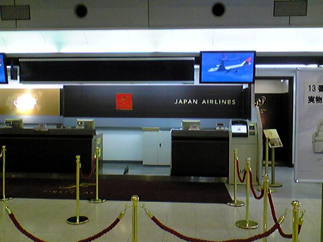 An airport check-in counter in black colour theme, with Japan Airlines written in capitals in white colour. There is a black carpet with the extra large letter 'F' in script font and 'JAL First Class' in smaller font, both in gold colour. The foreground has gold coloured poles with red velvet ropes