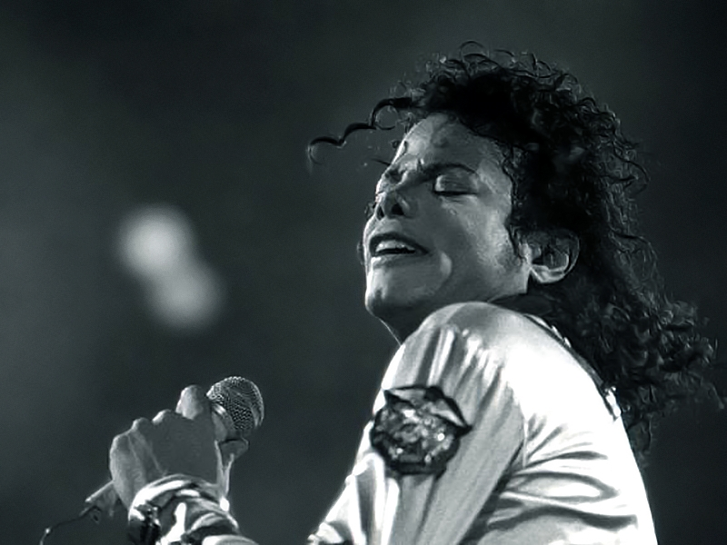 Black and white photo of Jackson holding a microphone and singing
