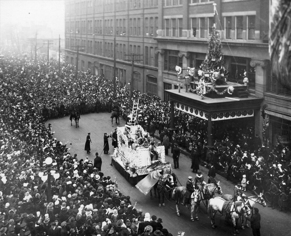 Eaton's Santa Claus Parade, 1918, Toronto, Canada. Having arrived at the Eaton's department store, Santa is readying his ladder to climb up onto the building.
