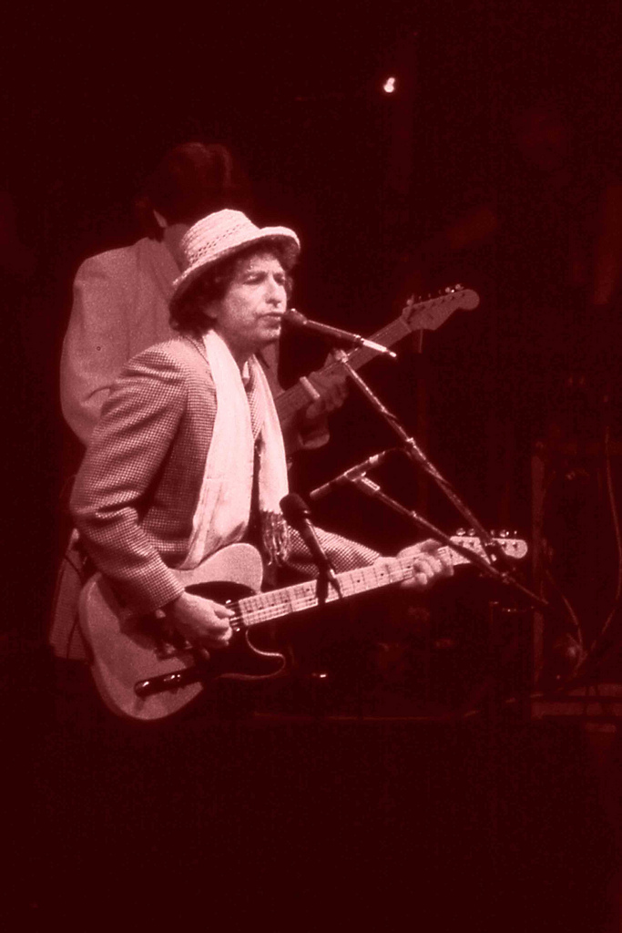 Dylan performing onstage with an electric guitar.