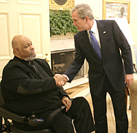 Two men in suits, facing one another and shaking hands; one is seated in a wheelchair.