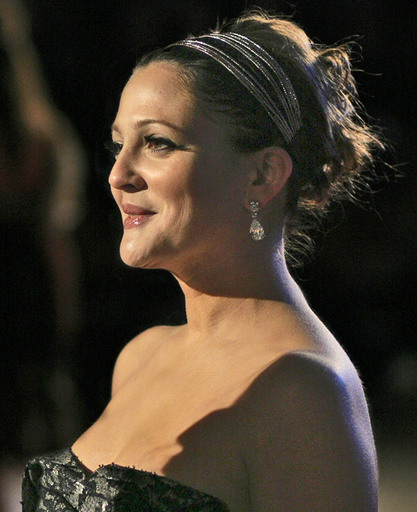 Head and shoulders shot of a smiling Barrymore with her hair up, wearing a strapless black dress.
