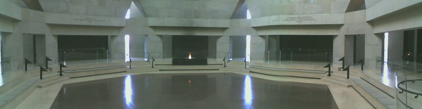 Panoramic view of the Hall of Remembrance. Hexagonal room with red-tile floor, limestone walls, and black panels. Eternal flame in foreground supported by a black box containing ashes from European Concentration Camps.