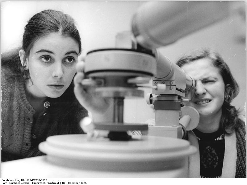 Two physics student stare at or in a Goniometer-Spectrometer