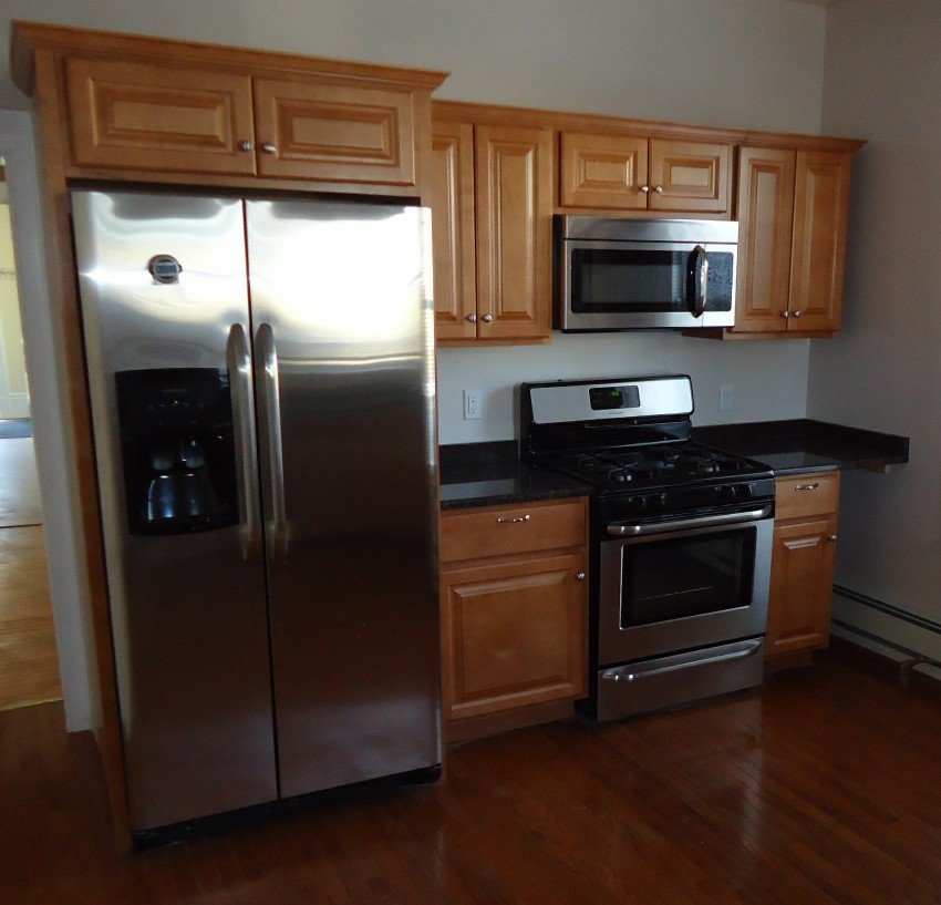 Renovated Kitchen With Cabinets Refrigerator Stove And Hardwood Floor