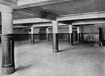 A black-and-white photo of an unfurnished basement, horizontally lit with diffuse light. It has a pale coffered ceiling, with thickish round pillars supporting the intersections of the beams. The lower half of both pillars and walls is covered with dark wood panelling. The bare floor is pale grey.