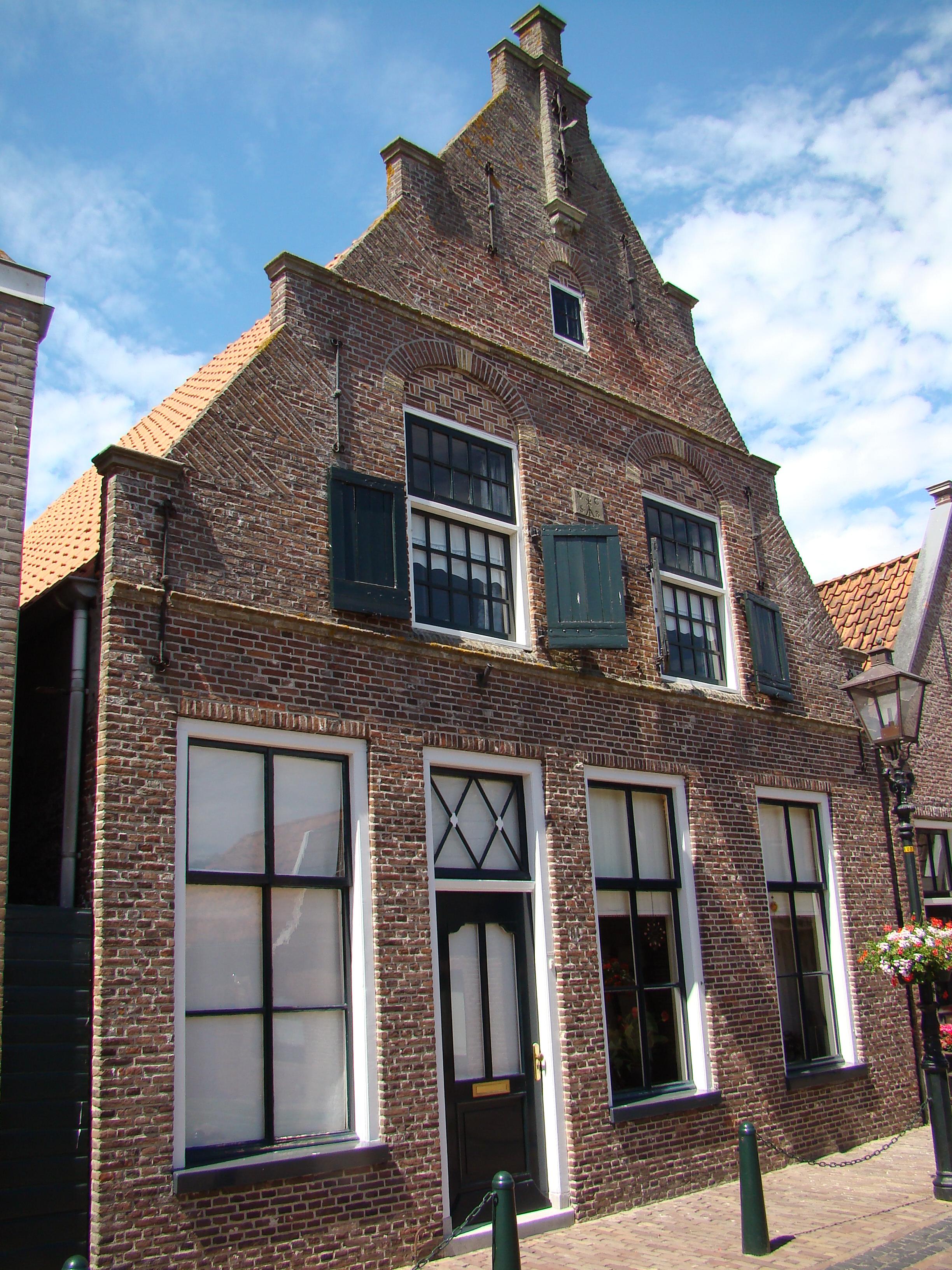 huis met gerestaureerde bakstenen puntgevel met enkele trappen waterlijsten zandstenen