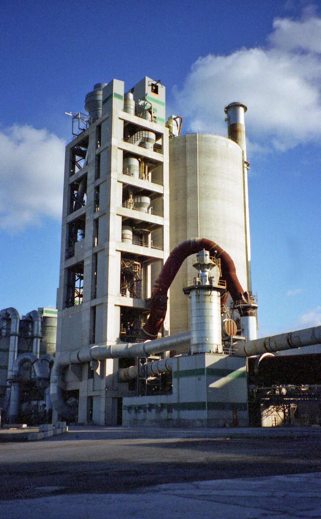 A preheater tower, rawmix silo and exhaust stack. Bottom left: rawmill. Bottom right: rotary kiln with tertiary air duct above. The U-shaped duct leading from the kiln inlet is an