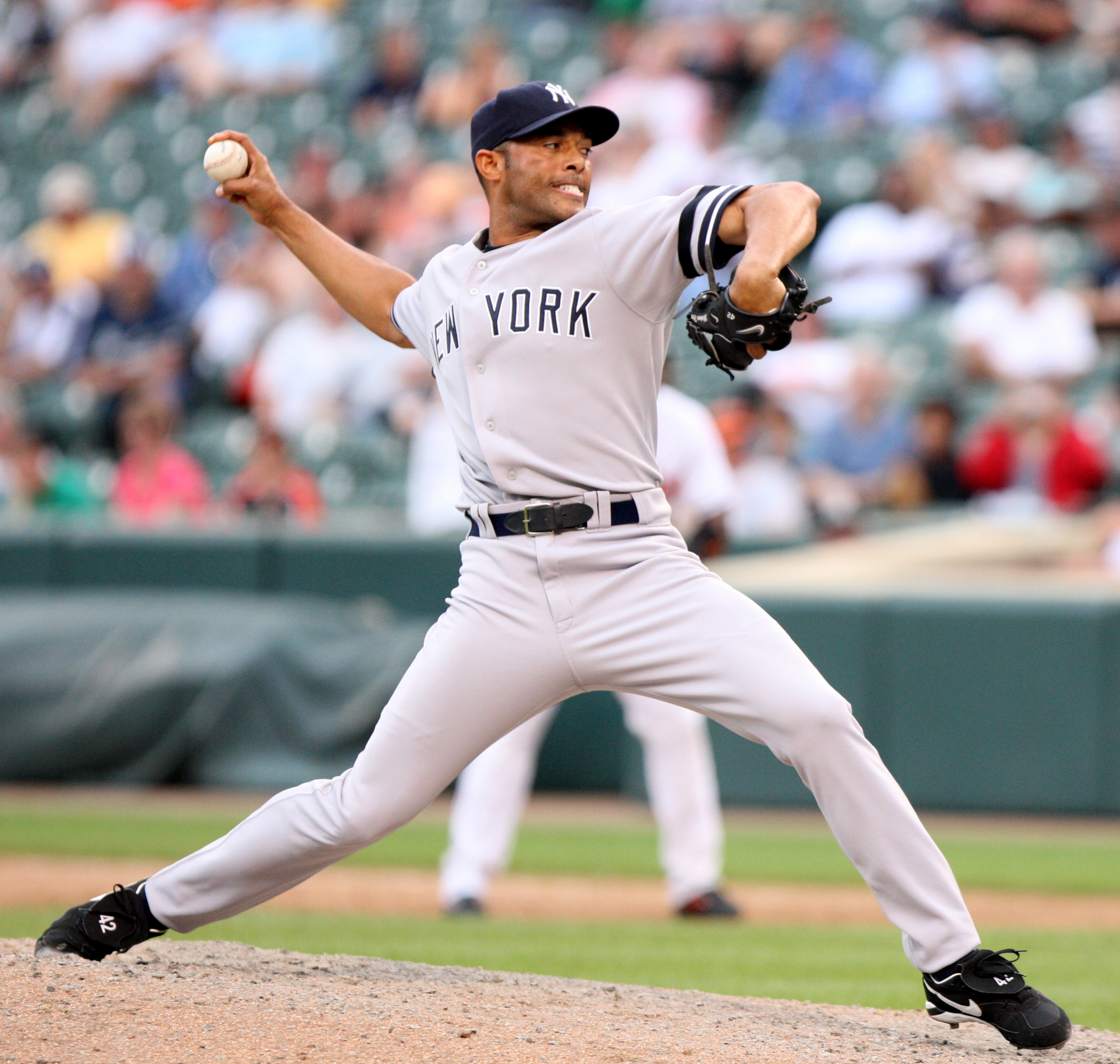 "Mariano Rivera in a gray baseball uniform and navy blue cap stands on a dirt mound. He is striding forward to the right as he clutches a baseball behind his head. His uniform reads ""New York"" in navy blue letters across the chest. His face is contorted in concentration."