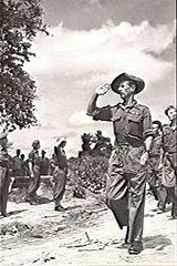 A marching soldier, in full military uniform and slouch hat, leading several other soldiers. He is saluting a stationary group to his right.