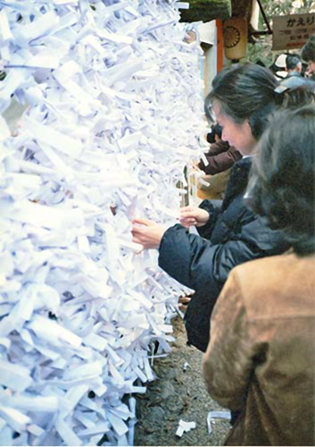 A woman tying her fortune written on a white piece of paper (omikuji) to a frame at Kasuga Shrine KasugaTaisha2.jpg