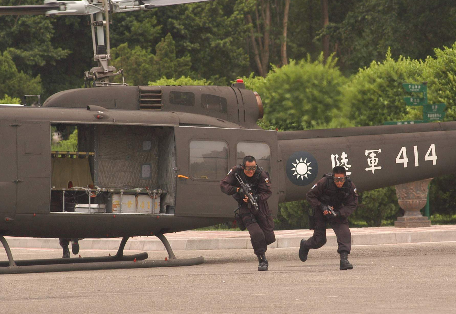 Two men in military uniform getting off an helicopter. They are both running and carrying a weapon.