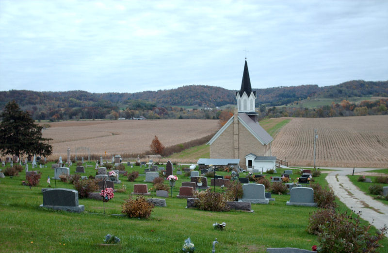A graveyard with more modern gravestones, kerbed memorials and cremation memorials as part of it