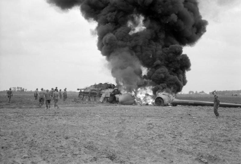 A C-47 aircraft, hit by A/A fire while returning from Market-Garden drops, crashes into a knocked out Jagdpanther near Geel