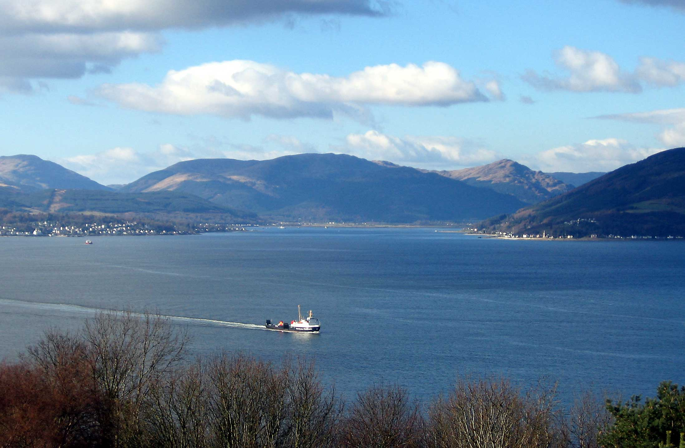 The Holy Loch seen across the upper Firth of Clyde from Gourock, with Hunter's Quay to the left and Strone to the right, with the Caledonian MacBrayne ferry <!-- MV --> arriving from Dunoon.