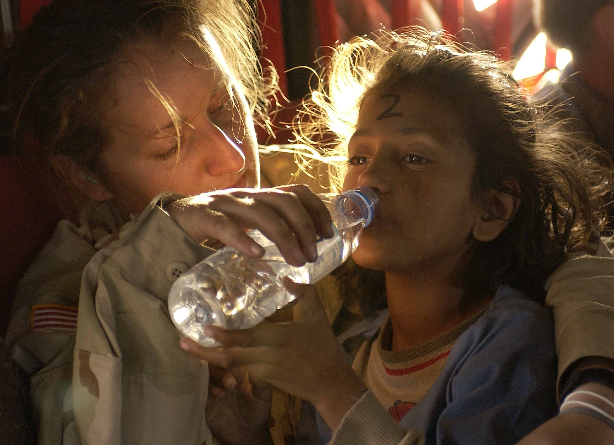 An American solider provides water to a Pakistani girl, October 2005
