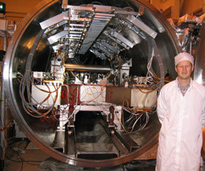 Man in white standing in front of a large machine