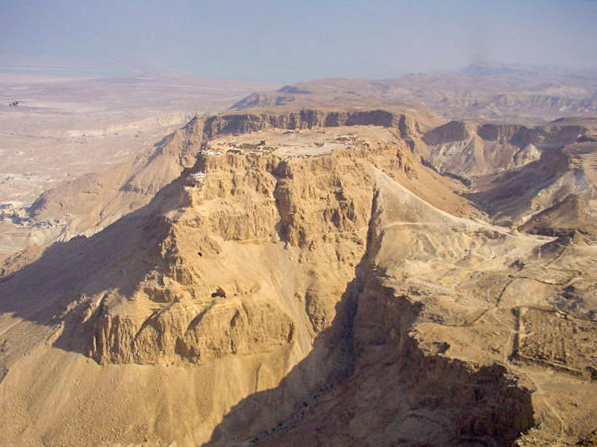 Ruins on the flat top of a sand colored mountain, surrounded by desert. Other mountains are visible in the background.