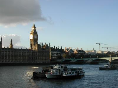 A large clock tower and other buildings line a great river.