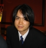 A 39-year-old Japanese man wearing a black suit coat, a blue tie, and a white button-up shirt. He has black hair and brown eyes, and is against a dark red background.