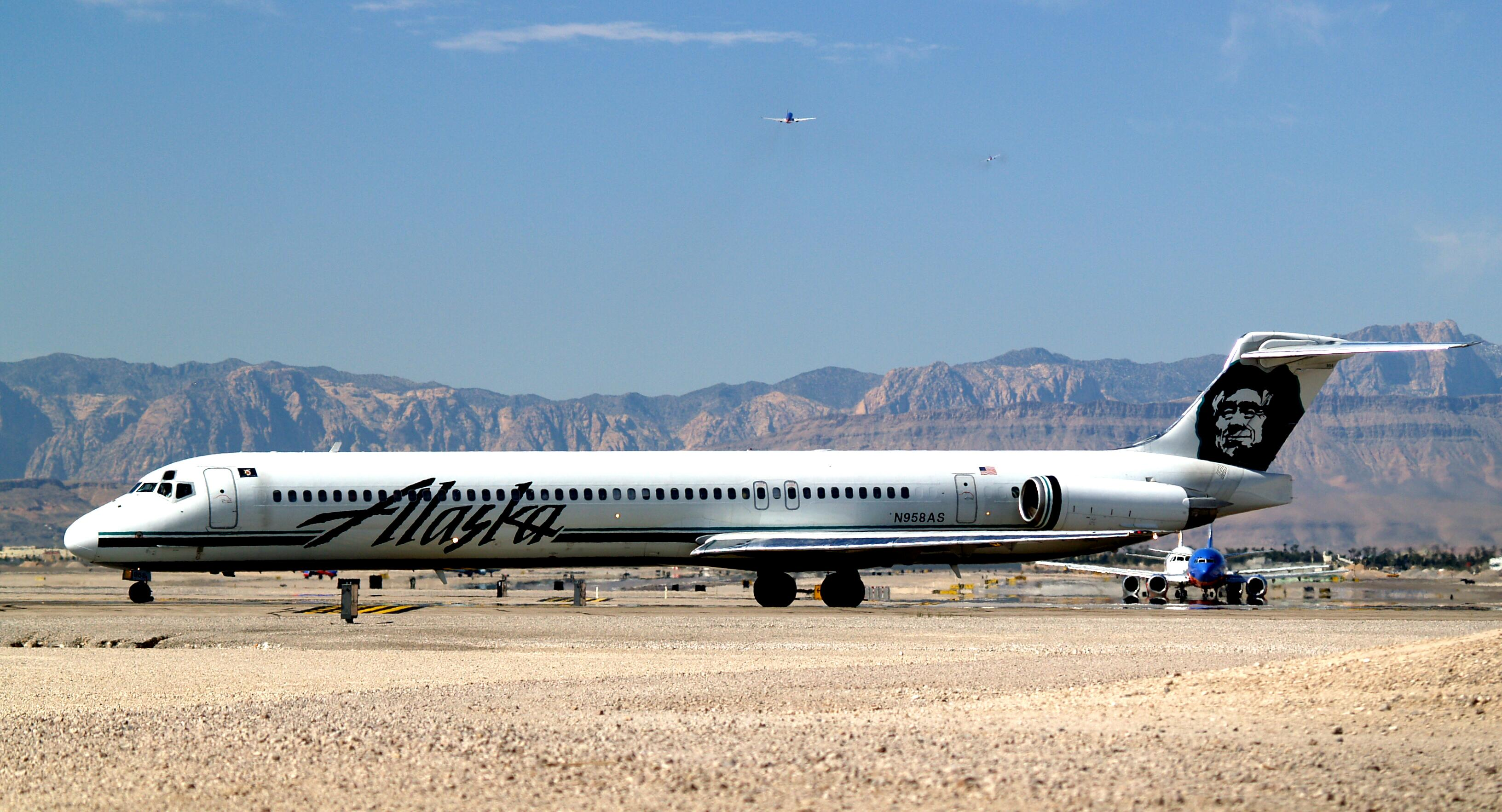 Right side view of an airplane taxiing on the ground towards left side of image.  Another plane is behind it, and in the background are mountains and blue sky with a few clouds.