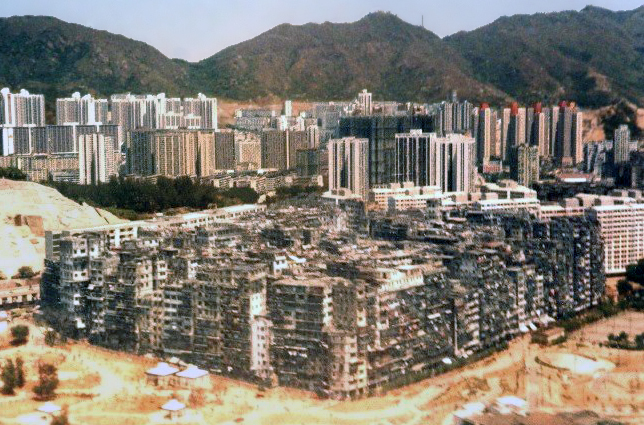 A large solid block of ramshackle buildings varying in height, with many taller buildings and some mountains in the background.
