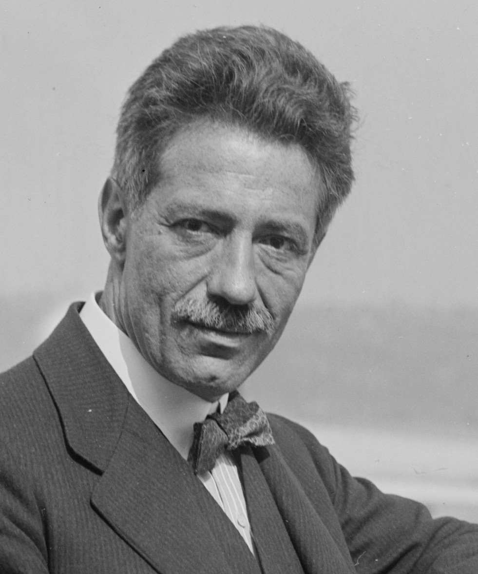 photograph of a middle aged man with a small moustache and bow-tie, looking towards the camera