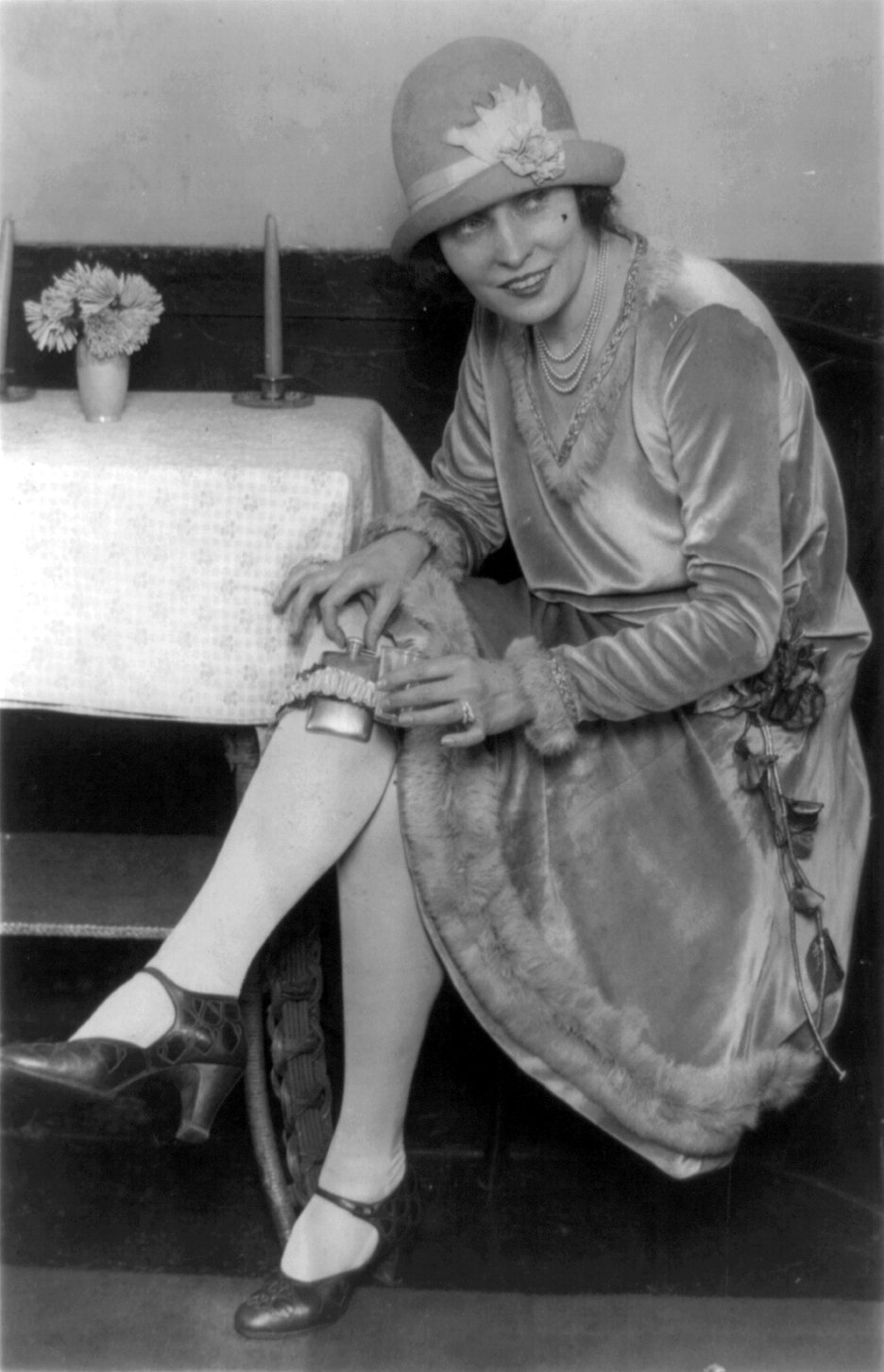 Mlle. Rhea seated with flask in garter on leg, 1926. Image via Wikimedia Commons