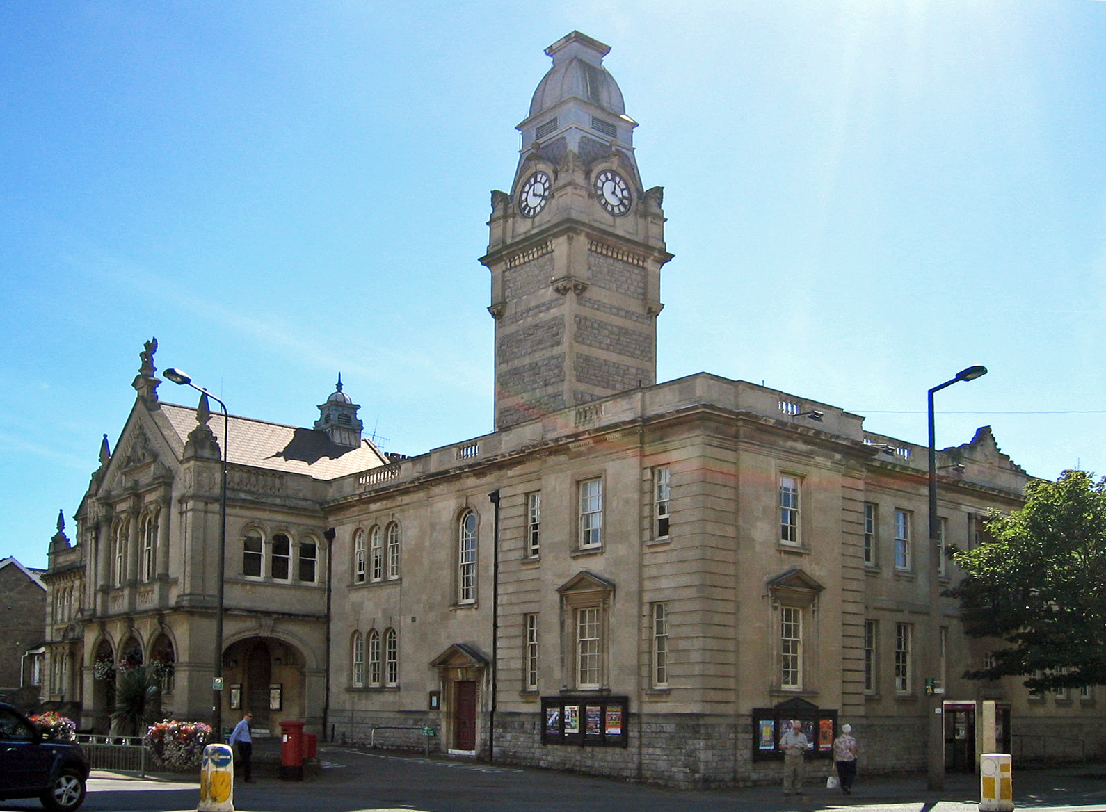 Stone building with colonnaded entrance. Above is a clock tower.