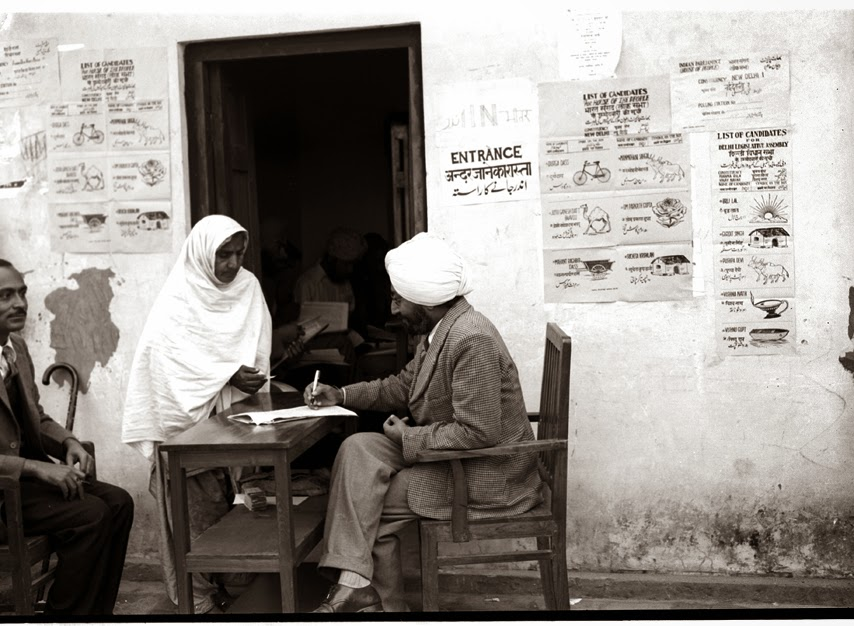A refugee woman being given her ballot papers after identification, at a polling station in Lajpat Nagar in 1952. Image courtesy: Photo Division, Ministry of Information & Broadcasting, Government of India/Wikimedia Commons [Public Domain].