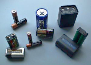 Various batteries (clockwise from bottom left): two 9-volt, two AA, triple AAA, one D, a handheld ham radio battery, a cordless phone battery, a camcorder battery, and one C.