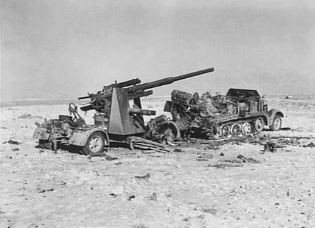 https://upload.wikimedia.org/wikipedia/commons/3/3b/Burnt-out_88_mm_Flak_36_near_El_Alamein_1942.jpg