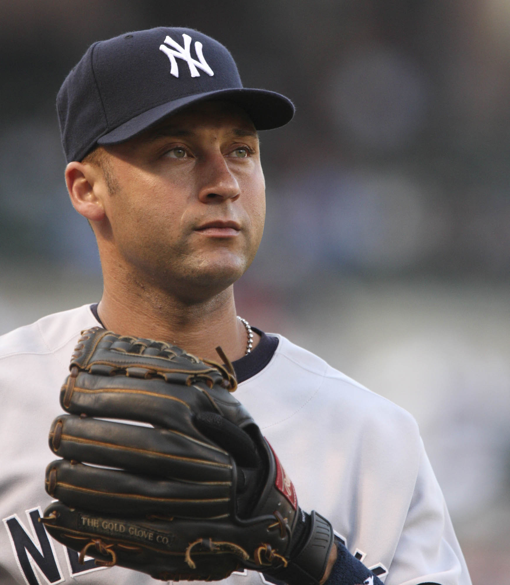 Derek Jeter wearing a navy hat and grey baseball uniform with a black glove stares into the distance.