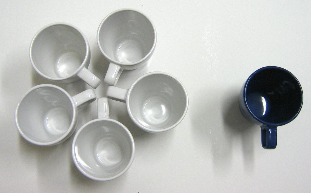 Imagem de um grupo de canecas brancas juntas, tendo ao lado uma caneca preta isolada. Imagem simboliza a exclusão social. | infantilidade