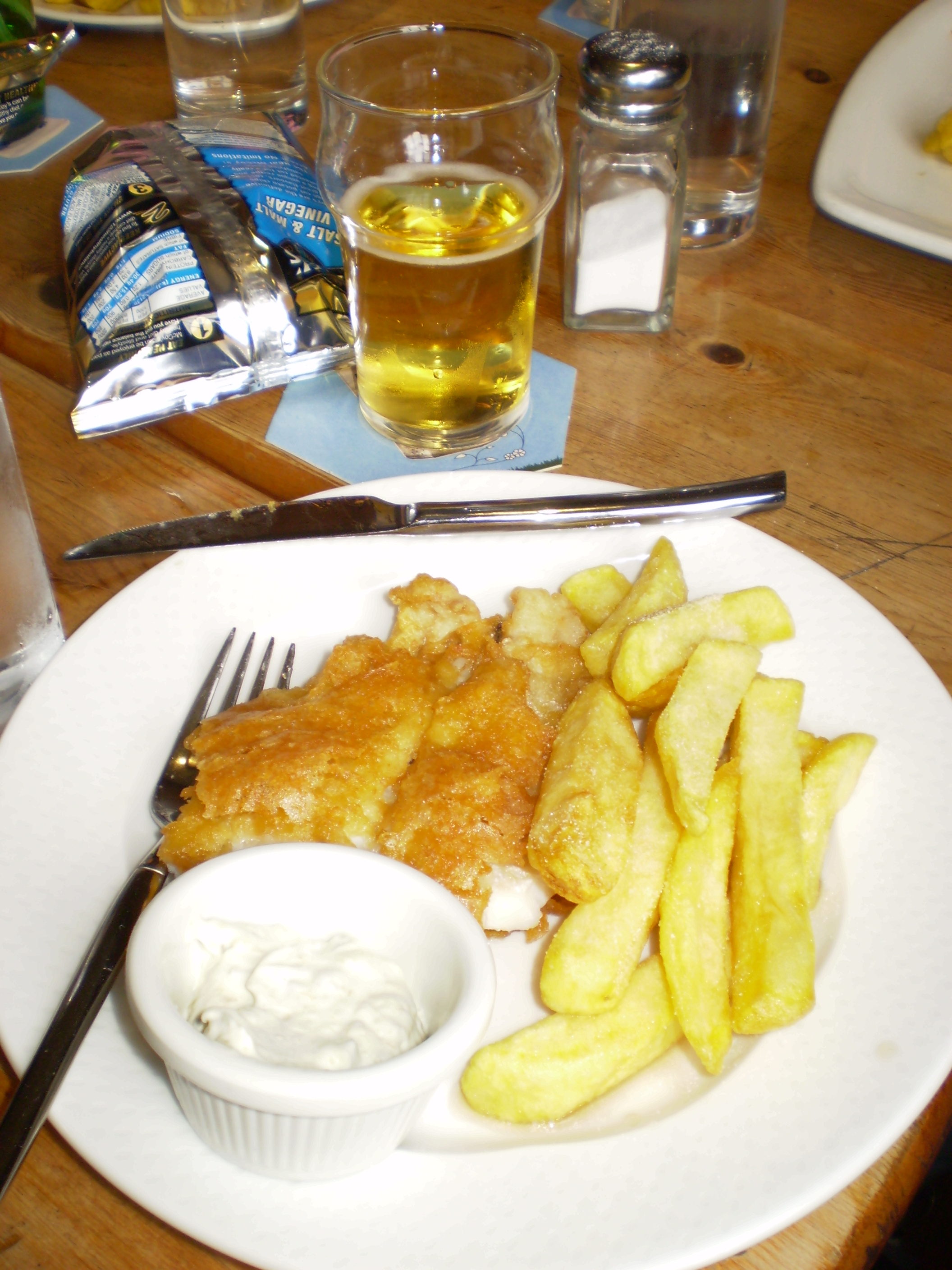 A round white plate with fried fish, french fries, a ramekin of tartar sauce with a glass of beer at the top of the plate.