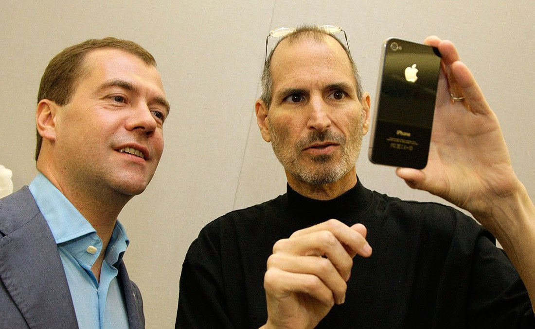 Shoulder-high portrait of two middle aged men, the one on left wearing a blue dress shirt and suitcoat, the one on right wearing a black turtleneck shirt and with his glasses pushed back onto his head and holding a phone facing them with an Apple logo visible on its back