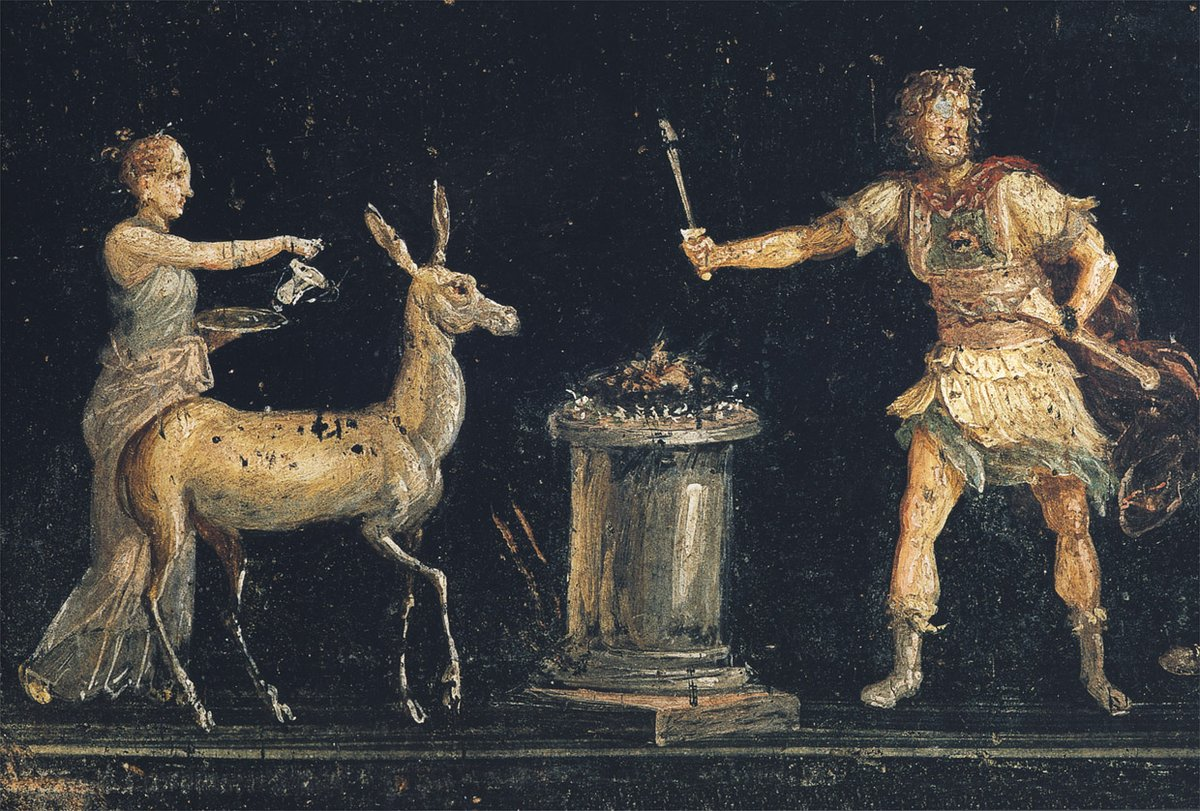 An ancient Fourth-Pompeian-Style Roman wall painting depicting a scene of sacrifice in honor of the goddess Diana; she is seen here accompanied by a deer. The fresco was discovered in the triclinium of House of the Vettii in Pompeii, Italy.
