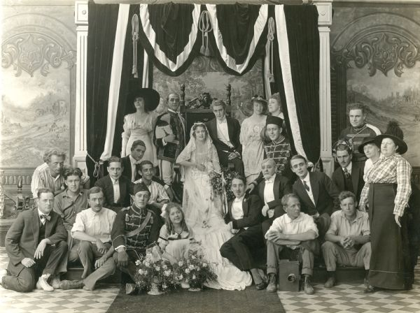 Production still of the cast and crew of the Universal silent serial The Broken Coin (1915). Grace Cunard and Francis Ford are in the center on the throne, the young actress Gertrude Short is seated on the floor in front of Miss Cunard, and John Ford is third from the left. A cameraman, likely Harry McGuire Stanley, is sitting (front right) with a Pathe film camera between his feet. Broken Coin 1915.jpg