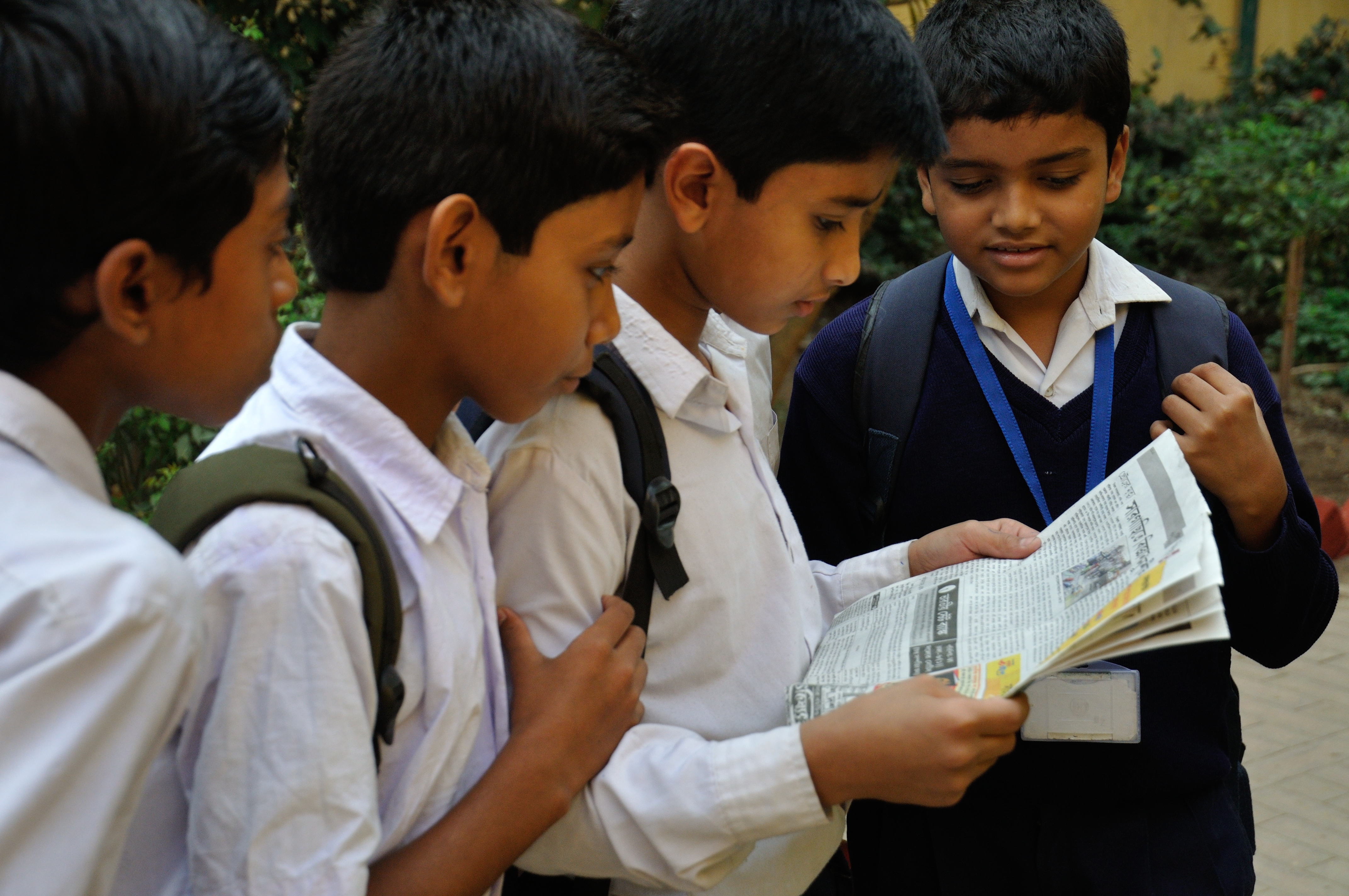 file:students reading newspaper - ramakrishna mission ashrama