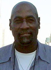 A black skinned man with a bald head and black goatee beard. He is wearing a light blue shirt with the top buttons undone, showing a white top underneath.