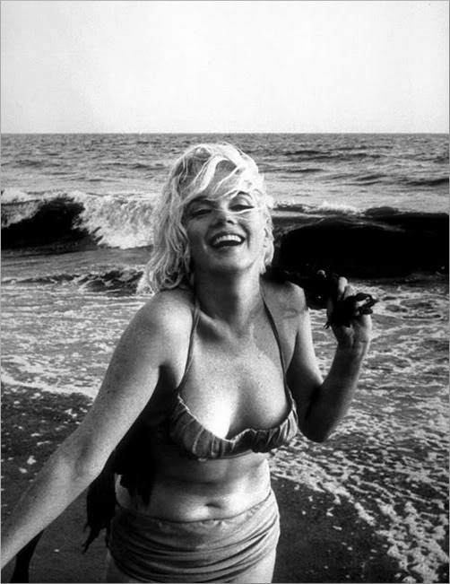 Monroe on a beach, wearing a bikini and laughing.