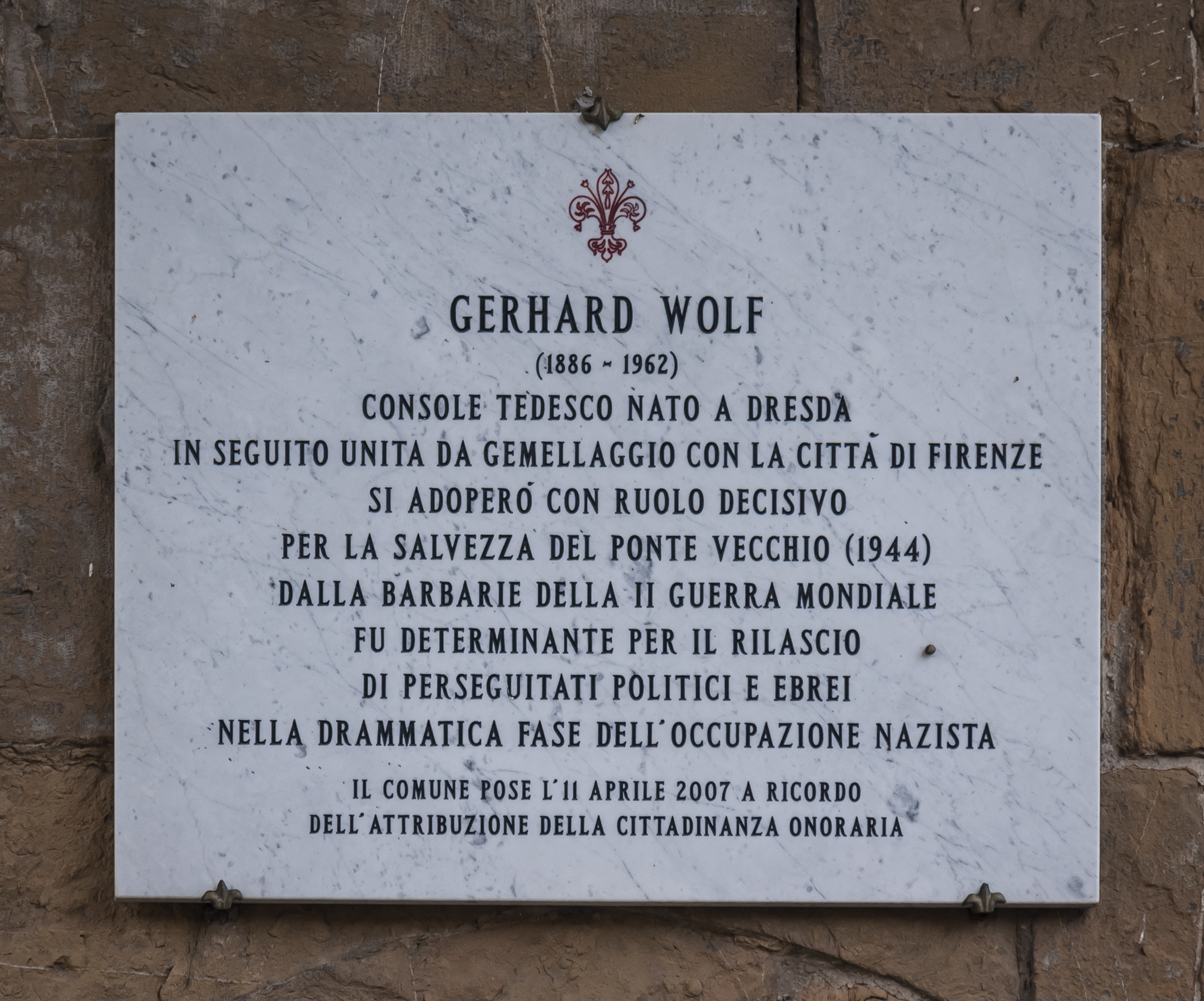 """The plaque in Italian reads: """"Gerhard Wolf (1886–1962). German consul, born at Dresden—subsequently twinned with the city of Florence—played a decisive role in the salvation of the Ponte Vecchio (1944) from the barbarism of the Second World War and was instrumental in rescuing political prisoners and Jews from persecution at the height of the Nazi occupation. The commune places this plaque on 11 April 2007 in memory of the granting of honorary citizenship."""""""