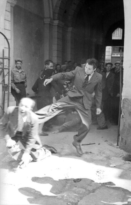 Rioter kicking a Jewish civilian next to a German guard post during a pogrom. Lviv, Nazi-occupied Ukraine. June 30, 1941. [537x800]