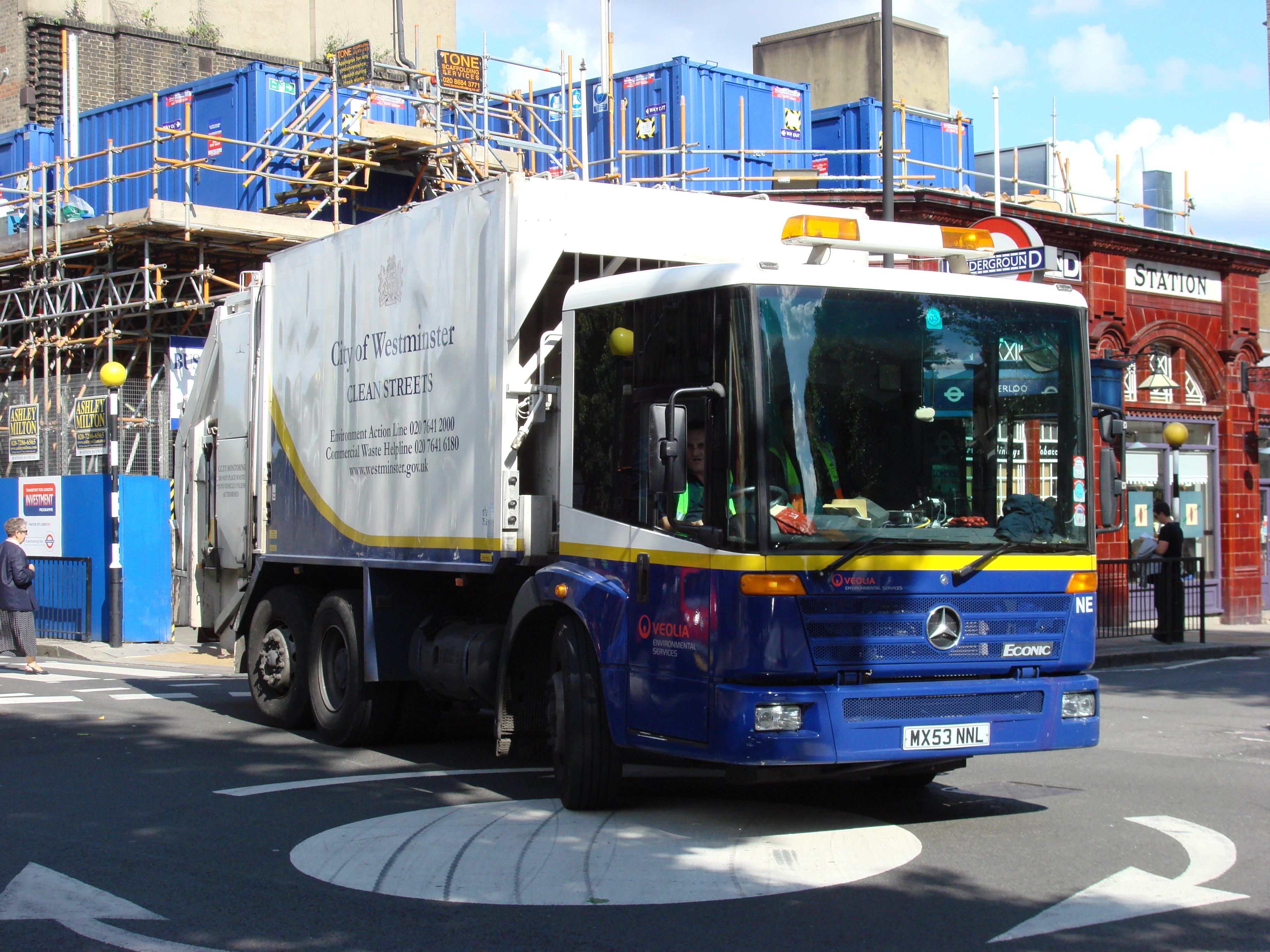 "A large six-wheeled lorry operated by the ""City of Westminster"", with a waste disposal unit at rear, drives across a small roundabout at the corner of a busy junction"