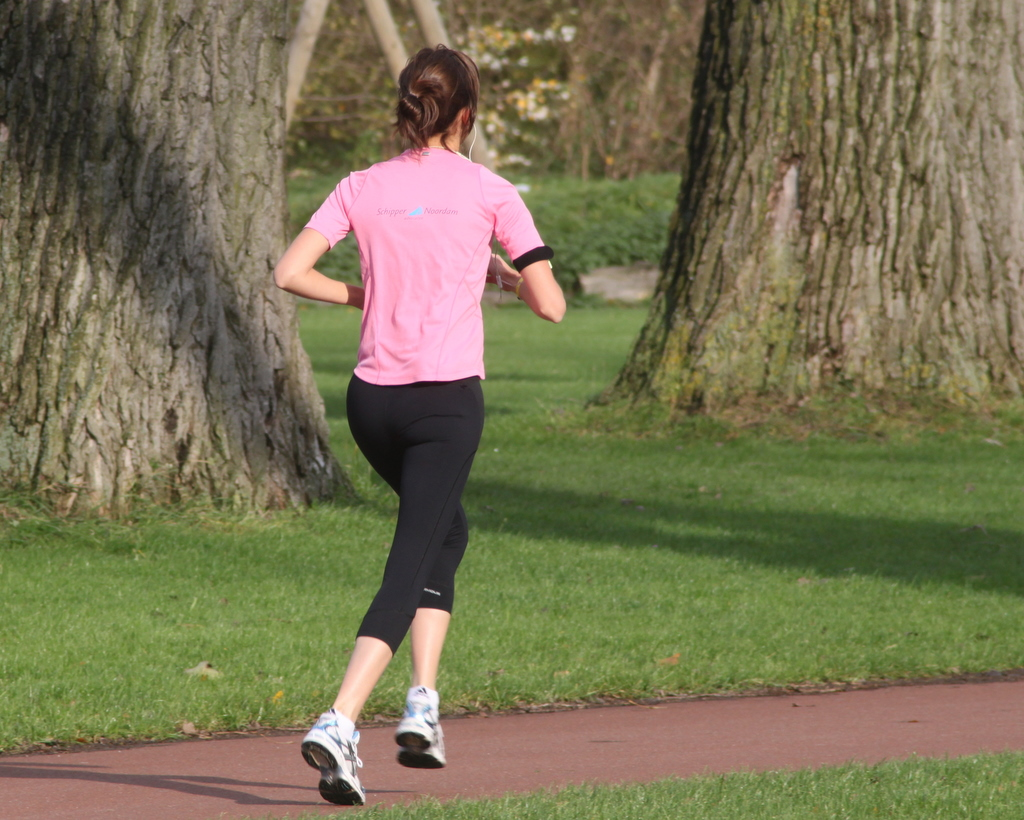 Image depicts a woman running through a park.