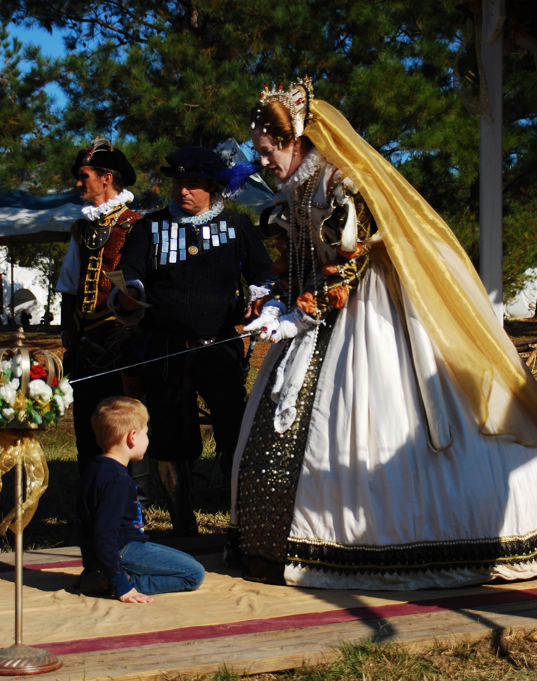 A Renaissance Festival enactment of Queen Elizabeth knighting a boy
